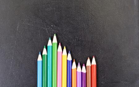 Colored Pencil Arrangement Against Chalk Board photo