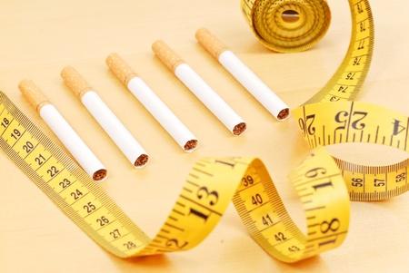 Rij van sigaretten omgeven door meetlint Stockfoto