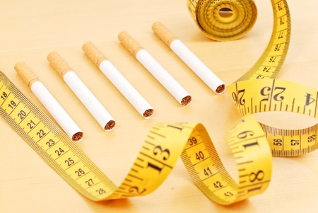 urge: Row of Cigarettes Surrounded By Tape Measure