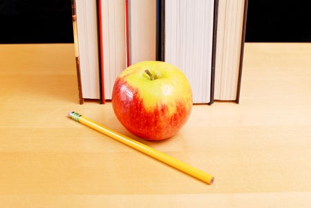 Apple with School Books on Table photo