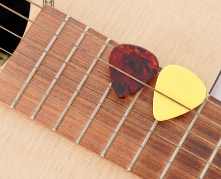 thin shell: Two Guitar Picks in between Acoustic Strings
