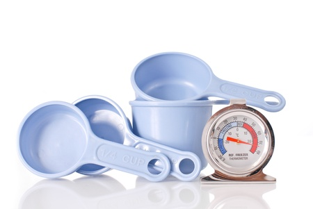 measuring cup: Cooking Thermometer with Four Measuring Cups Stock Photo