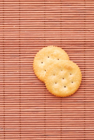 two crackers on brown bamboo mat