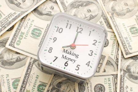 provisions: Clock with Making Money Caption on a Pile of Hundred Dollar Bills Stock Photo