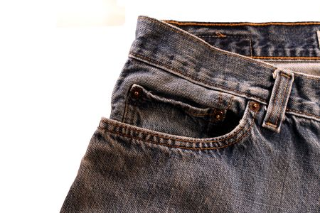closeup of blue jeans waist and pocket on a white background