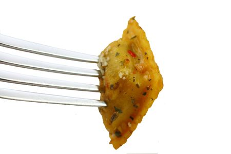 Cooked ravioli on a fork isolated on a white background