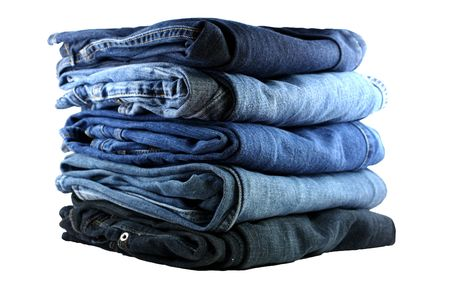 stack of five various shades of blue jeans on a white background Stock Photo