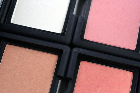 closeup of four colored blush makeup compacts