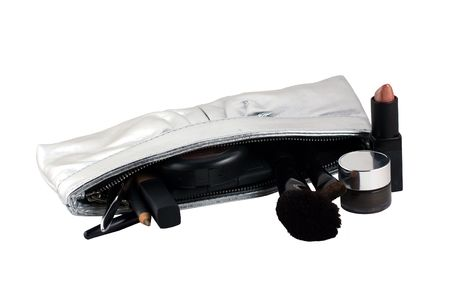 a variety of makeup with a silver clutch on a white background