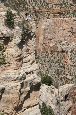 A group of people leaning over the edge of the Grand Canyon