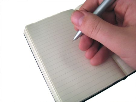 A hand writing in a journal/notebook with a pen isolated on a white background. Stock Photo - 2458008