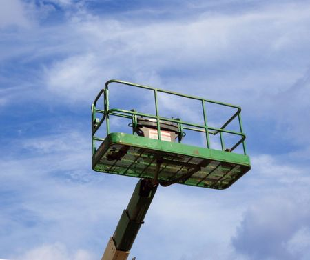 A green mechanical lift on top of a cloudy blue sky