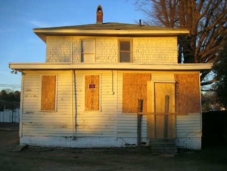An old house with boards in the windows. Stock Photo