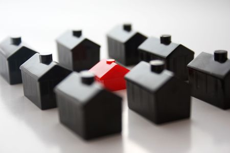 conform: Rows of black plastic toy houses with one smaller red one in the middle, standing out.