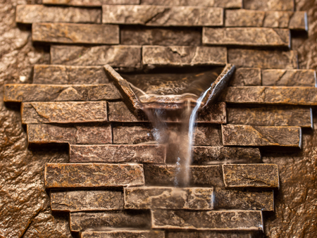 Background of golden brown stone bricks with water falling from spout protruding from center
