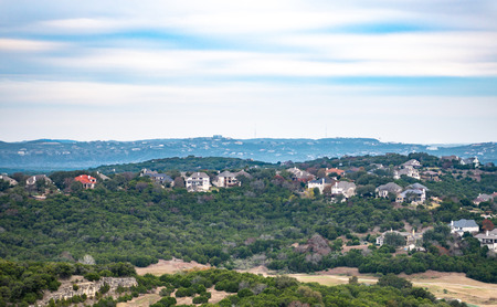Landscape of homes nestled in trees, built into hill country of Austin, Texas with rock cliff face visible and more homes in distant background