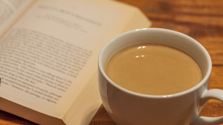 A white ceramic cup of coffee with cream next to a book, sitting atop a wooden coffee table