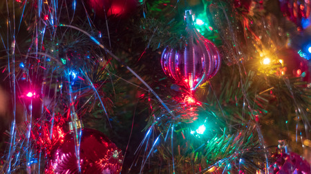 Brightly colored, cheery Christmas tree ornaments hung up with lights and tinsel