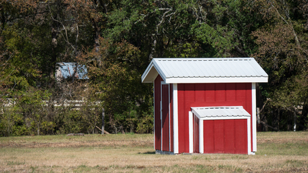 Small red and white shed in grassy field