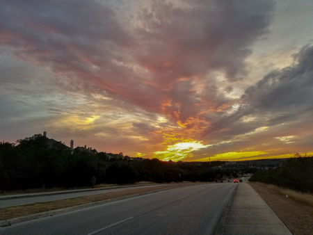 Sunset in Texas seen from side of road with cars passing by