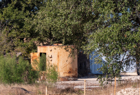 Old building and steel tank, textured surface with steel door and rust