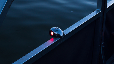 Front bow bi-color boat light showing the red port side, as required by regulations.