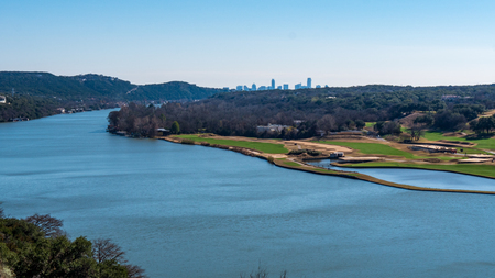 View from a tall hill of a river near Lake Travis with view of Austin skyline visible far away