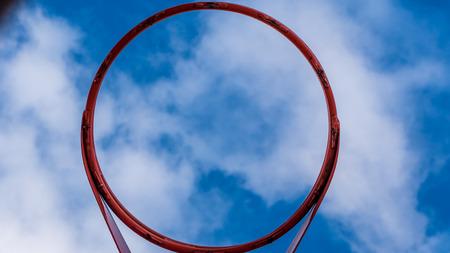 Upwards view of basketball hoop against a bright blue sky 版權商用圖片