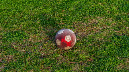 White and red soccer ball resting on the ground at a park in the golden hour sun