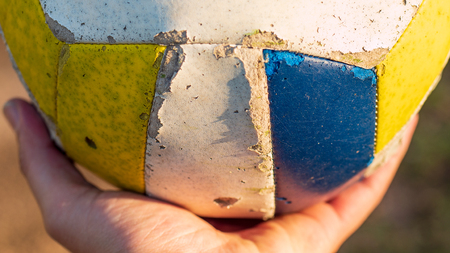 White, yellow and blue soccer ball resting on a hand during golden hour