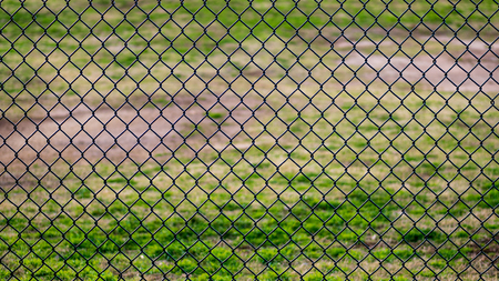 Chain link fence in a sports park with grassy field behind it Imagens