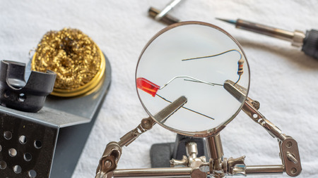Soldering a resistor and LED with a magnifying glass, with alligator clips holding the components Фото со стока