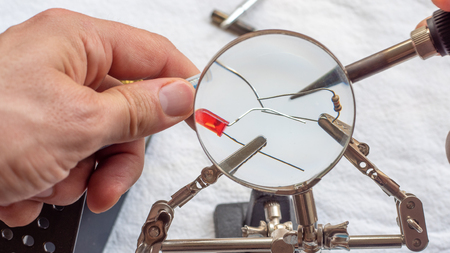 Soldering a resistor and LED with a magnifying glass, with alligator clips holding the components Archivio Fotografico