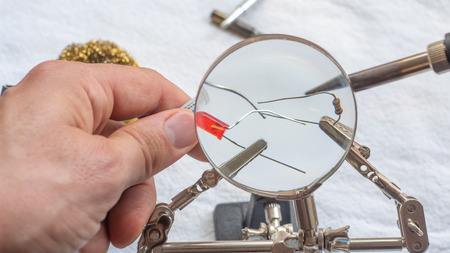 Soldering a resistor and LED with a magnifying glass, with alligator clips holding the components 版權商用圖片
