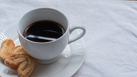 Cup of Greek or Turkish coffee, on small white saucer plate, with two cookie pastries, on white cloth surface