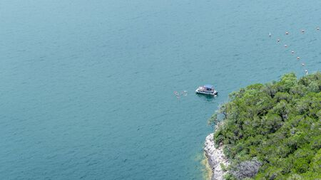 Pontoon boat anchored near the shoreline of a lake, with occupants swimming 版權商用圖片