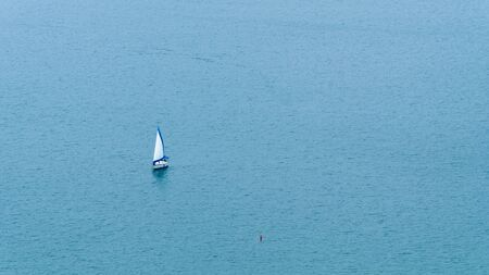 Small white and blue sailboat on calm, open blue water with small red buoy nearby 版權商用圖片