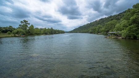 View down river from the middle of the river, with green trees on either side and clouds above
