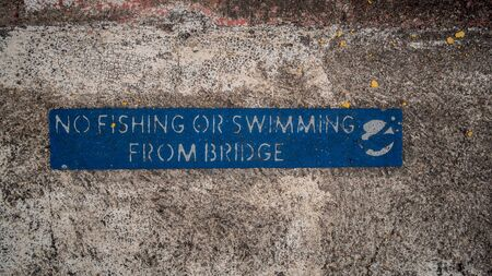 Blue No Fishing or Swimming From Bridge Sign on Weathered, Aged Concrete