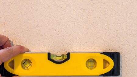 Yellow bubble level showing bubble in the level position to indicate a flat plane, resting against a white painted wall