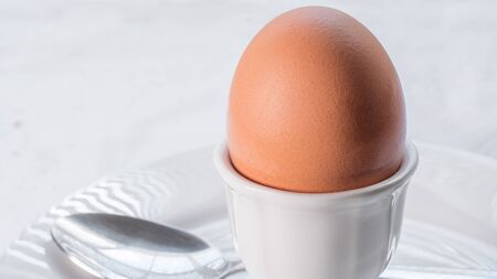 Soft boiled brown egg in a white ceramic egg cup, on a white ceramic plate with a spoon, on a white cloth tablecloth