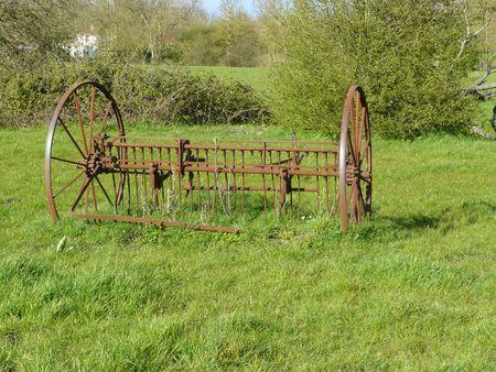 arbres: Roues de machine agricole ancienne avec rateau, sur un pré Stock Photo