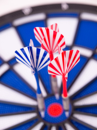 Dartboard with two red darts and one blue dart boked