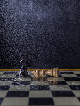 Chess figures on a dark background in the rain. Lose and win concept. Selective focus