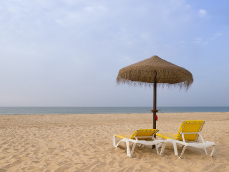 Beach scene with sunbeds and straw umbrella. Summer beach vacation concept Banco de Imagens