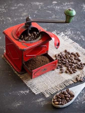 vintage red coffee grinder and coffee beans with wooden spoon