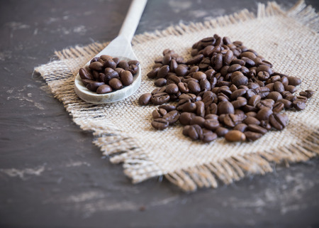 coffee beans background with wooden spoon selective focus