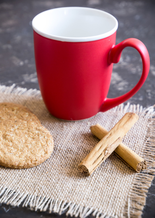red coffee cup, cinnamon stick and cakes