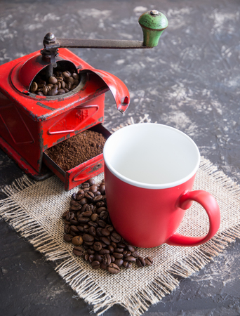 Vintage red coffee grinder, red cup, with coffee beans
