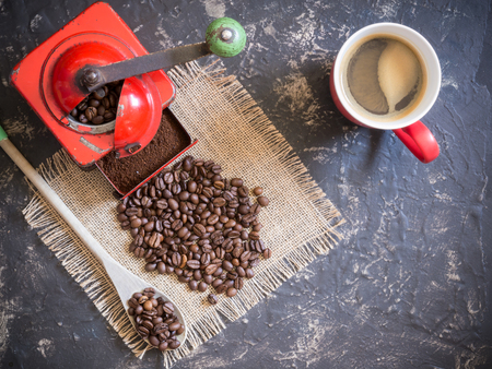 scene about coffee in top view. Vintage red coffee grinder, red cup, wooden spoon and coffee beans Banco de Imagens